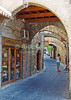 Rhodes Town, on the island of Rhodes, Greece.  Tourists explore the shops that line a narrow street, framed by arches supporting the old battlements and keep inside the Crusader castle at Rhodes Town.  © Rick Collier<br /> <br /> <br /> <br /> <br /> <br /> Greece Rhodes tour tourism tourist tourists citadel fort fortress castle crusader crusaders knight knights templar templars wall walls sidewalk window windows shop store shops stores sidewalk street alley arch arches walk walking