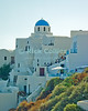 Oia Town, Santorini, Greece.  The blue dome of a Greek Orthodox church tops a collection of homes and shops that seem to be built directly on top of one-another.  Santorini is one of several islands that ring the blown-out remains of an ancient volcano, rising from the deep ocean in the Aegean Sea.  The volcano exploded, leaving several islands surrounding a very deep patch of sea -- actually once the caldera of the volcano.  The two large towns on Santorini, Oia and Fira towns, overlook the caldera.  © Rick Collier<br /> <br /> <br /> <br /> <br /> <br /> Greece Santorini Oia Greek Orthodox church chapel cliff cave home caldera Aegean Sea ocean sun stairs steps bright colors door doors window windows patio porch wall