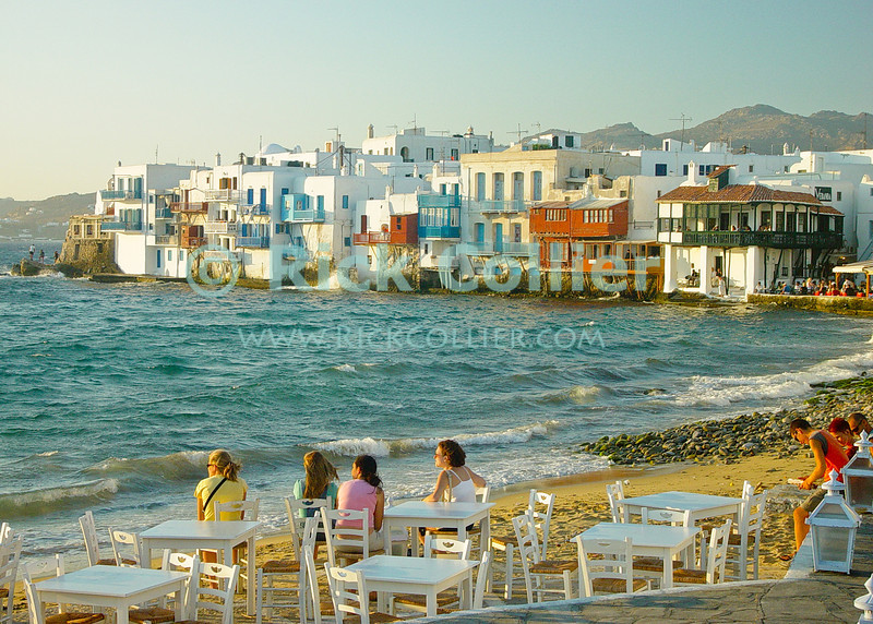 Mikonos, Greece.  Visitors at a cafe watch the sunset and enjoy the view of colorful Mikonos houses, cafes, and restaurants that stand directly at the sea's edge.  © Rick Collier<br /> <br /> <br /> <br /> <br /> <br /> <br /> Greece Mikonos Mykonos Greek balcony door window shutter alley alleyway overlook ocean view Aegean Sea waterfront bar beach sunset diner tour tourist tourism