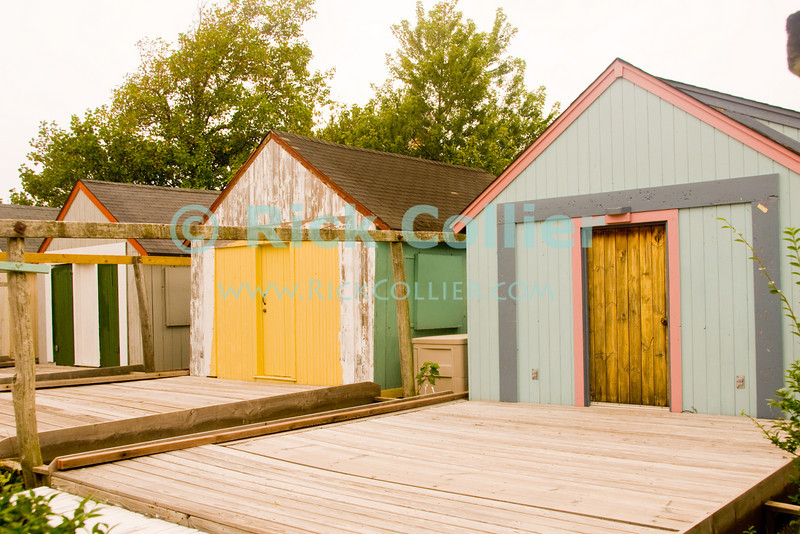 """""""Beach Shack and Deck)"""" - Where once there were seasonal tents, some have now built wooden """"shacks"""" where they can stay when visiting the beach in summer.<br /> <br /> <br /> USA """"New Jersey"""" NJ """"Ocean Grove"""" Ocean Grove sidewalk shack tent camping seasonal summer stay lodging property doors color colorful colors yellow deck decks green pink"""