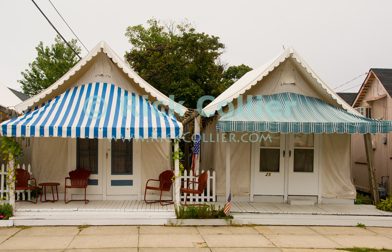 """""""Beach Property"""" - Seasonal tents with front awnings provide porch space by the sidewalk in Ocean Grove, New Jersey, USA.  The tents are used by their owners in season, providing their lodging for beach visits.<br /> <br /> <br /> USA """"New Jersey"""" NJ """"Ocean Grove"""" Ocean Grove sidewalk tent camping seasonal summer stay lodging property color colorful colors stripes striped awnings blue red tree shade"""