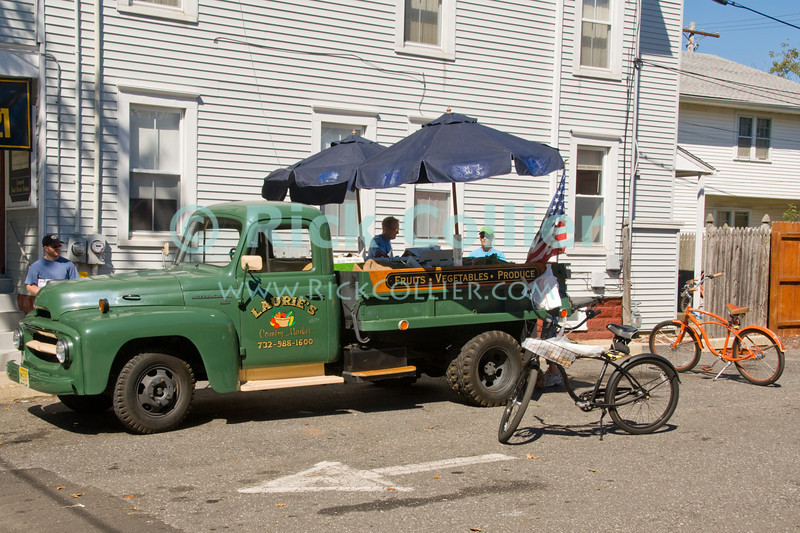 """Laurie's Produce"" - A roadside market pulls up on weekends in Ocean Grove, New Jersey.<br /> <br /> <br /> USA ""New Jersey"" NJ ""Ocean Grove"" Ocean Grove market green truck groceries fresh produce bicycle umbrella delivery"