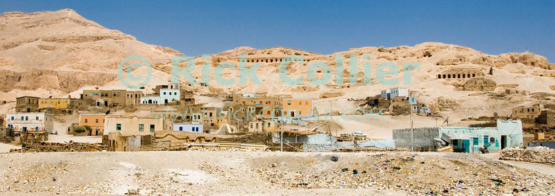 Egyptian town of Gurna, west bank of the Nile near Luxor, Egypt.  A poor Egyptian town stands in the shadow of ancient tombs, probably belonging to nobles and tomb builders to the kings interred in the Valley of the Kings, just on the other side of these mountains.  Though only kings and queens could be interred in the royal valleys, high nobles and the tomb builders were permitted to create their own burial places nearby.  The residents of these small towns are mostly the families of the original tomb-builders, who were the only people in ancient Egypt to reside on the west bank of the Nile River.  © Rick Collier<br /> <br /> <br /> <br /> <br /> <br /> <br /> Egypt Egyptian Karnak Luxor tourist tourism history historic antiquity antiquities Thebes Theban Thebian Nile 'Nile River' temple tomb monument souvenir shop town village 'Valley of the Kings' necropolis