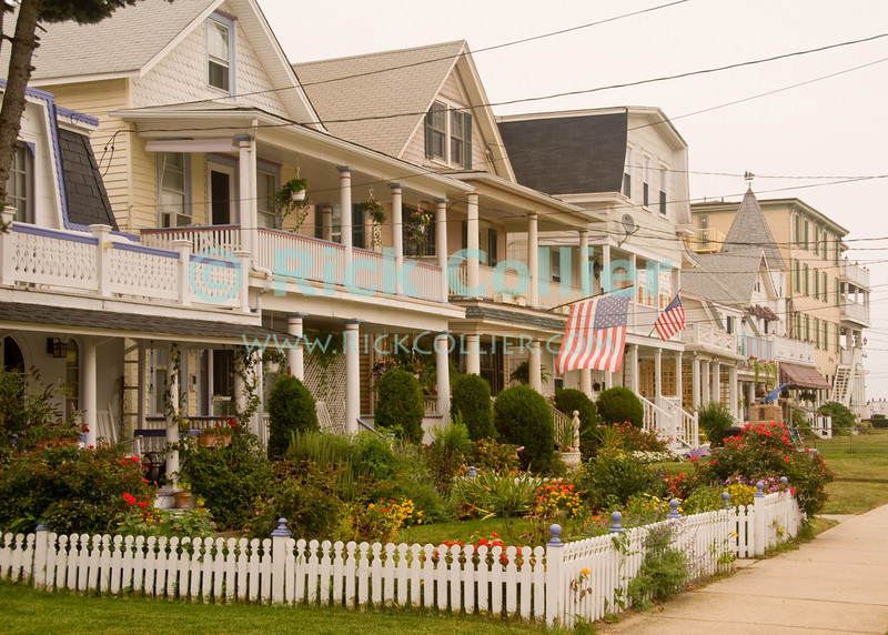 """""""Yard"""" - Picket fences and flags decorate beautifully kept houses line a beach-block street at Ocean Grove, New Jersey, USA.<br /> <br /> <br /> USA """"New Jersey"""" NJ """"Ocean Grove"""" Ocean Grove sidewalk houses homes vacation summer beach block yard power lines neat decor flag flags fence fences garden"""