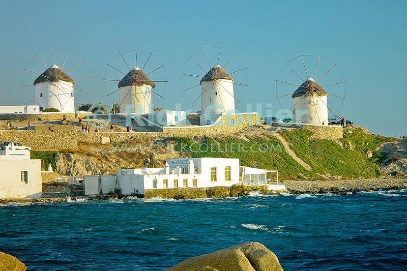 Mikonos, Greece.  Four of the famous windmills at Mikonos overlook a small restaurant and the sea.  © Rick Collier<br /> <br /> <br /> <br /> <br /> <br /> <br /> Greece Mikonos Mykonos view ocean Aegean sea windmill
