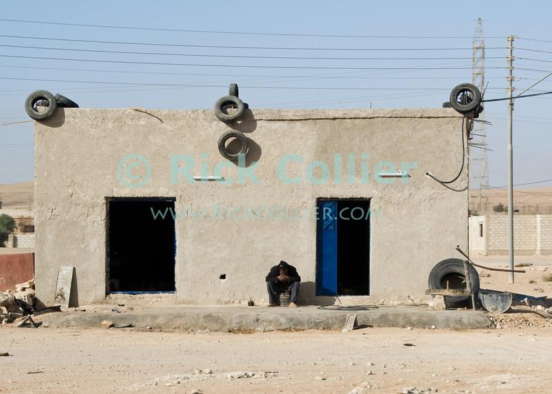 """Blue Door"" -- A small shop by the side of the ""desert highway,"" south of Amman Jordan.  © Rick Collier<br /> <br /> <br /> <br /> Jordan arab bedouin arabic country building house home shop concrete tire sleep shutter desert"
