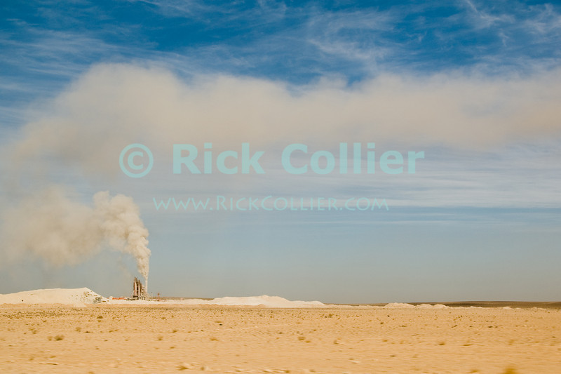 A dust plume rises from a cement factory, in the high desert south of Amman, Jordan.  © Rick Collier<br /> <br /> <br /> <br /> <br /> Jordan desert sand cement factory dust plume cloud wind blow