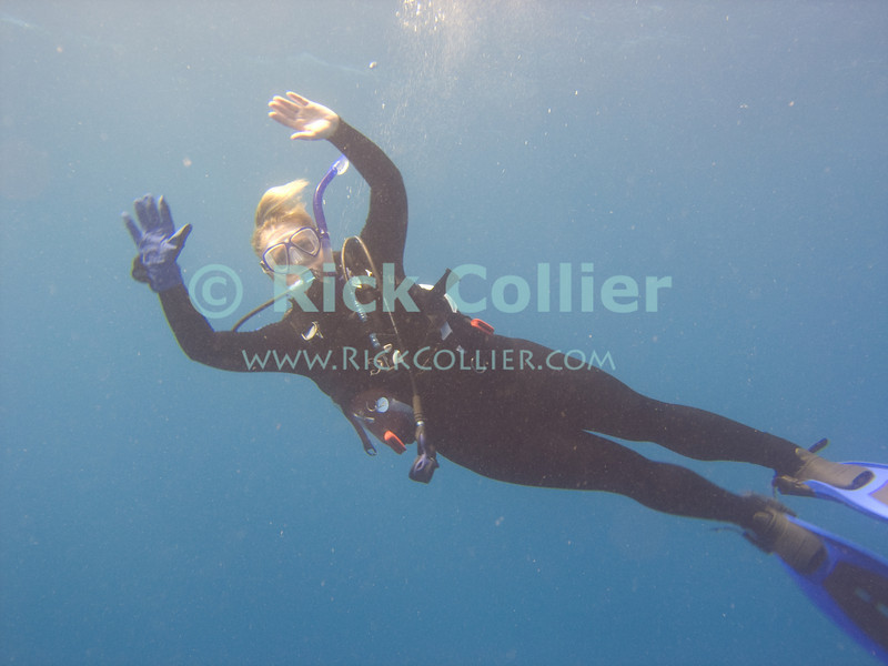 St. Eustatius (Statia) Underwater - A scuba diver (Nancy) practices bouyancy control in mid-ocean.  Notice the one glove, which indicates she is coming up a dive.  Gloves are prohibited in the protected waters of Statia (a marine park), but divers often wear one glove to protect their hand while ascending fixed mooring lines.  © Rick Collier