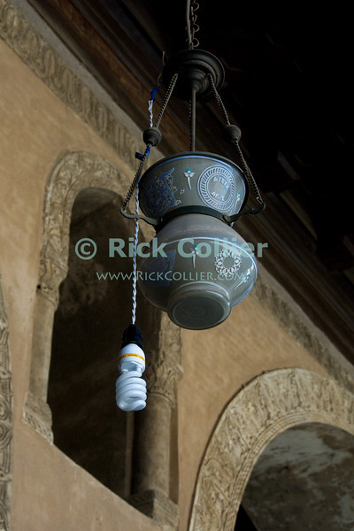 """Cairo, Egypt -- A more recent addition augments the old lamps in the historic ibn Tulun mosque.   © Rick Collier / RickCollier.com<br /> <br /> <br /> <br /> travel; vacation; tour; tourism; tourist; destination; Egypt; Cairo; mosque; madrassa; Tulun; """"ibn Tulun""""; light; lamp"""