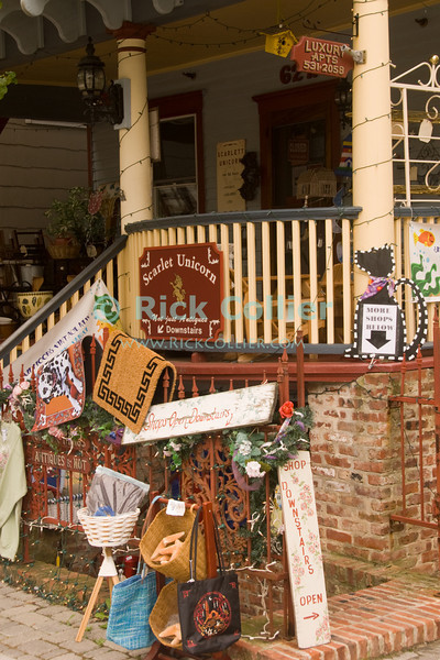 """Apartments upstairs"" -- A small basement shop displays its wares.  Ocean Grove, New Jersey, USA.<br /> <br /> <br /> USA ""New Jersey"" NJ ""Ocean Grove"" Ocean Grove street scene shop store market apartment stair rail banister advertising storefront sidewalk display"