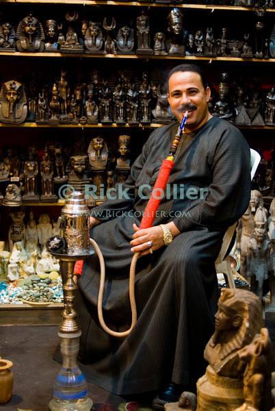 """Khan el-Khalili bazaar, Cairo, Egypt -- Local residents and shopkeepers are friendly and relaxed in the Khan el-Khalili bazaar.  Many are happy to talk with any visitor, while smoking flavored tobaccos in the ubiquitous hookahs (or """"shisha"""") that are found nearly everywhere.  (Subject permission / release is available.) © Rick Collier / RickCollier.com<br /> <br /> <br /> <br /> <br /> travel; vacation; destination; Egypt; Cairo; night; Khan; """"Khan el-Khalili""""; bazaar; market; marketplace; lights; shops; stalls; vendors; portrait; hookah; shisha; pipe; smoking; shop; shopkeeper; smile; friendly"""