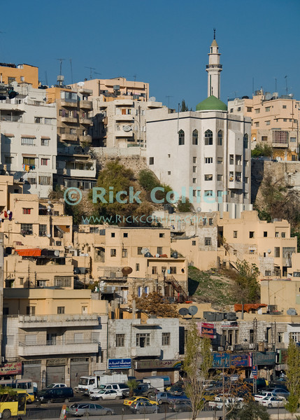 Hills of Amman.  A towering mosque (with a green domed roof and minaret) overlooks residences, shops, and the main street in old, Islamic Amman Jordan.  © Rick Collier<br /> <br /> <br /> <br /> <br /> <br /> <br /> Jordan Amman Rome city Islamic buildings apartments 'city center' street mosque