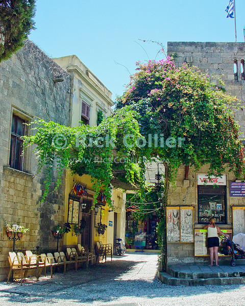 Inside the Crusader citadel, Rhodes Town, on the island of Rhodes, Greece.  Chairs wait in the shade, to be used when a taverna opens in the square.  © Rick Collier<br /> <br /> <br /> <br /> <br /> <br /> Greece Rhodes tour tourism tourist tourists citadel fort fortress castle crusader crusaders knight knights templar templars street road alley shop store tavern taverna cafe restaurant