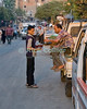 A laborer takes a cup of coffee or tea from a shop boy in the street.  At the end of the day in the Sharia Ahmed Maher (street) in the old city, Cairo, Egypt.  Cairo residents and shoppers come and go, sharing the street with trucks and cars as they make their way home with shopping at the end of the day. © Rick Collier<br /> <br /> <br /> <br /> <br /> <br /> <br /> Egypt Egyptian Cairo tourist tourism history historic antiquities Islamic mosque 'old town' 'walled city' vendor seller pedestrian walk resident Arab workers laborer truck street road coffee tea cup tray