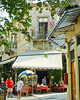 Athens, Greece.  Shops, cafes, and tavernas line the shaded streets of the Plaka.   © Rick Collier<br /> <br /> <br /> <br /> <br /> <br /> Greece Athens window windows shutter shutters flower flowers shop tavern taverna store cafe restaurant awning shade