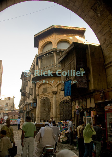 Islamic Cairo Street.  The streets of the original walled town of Cairo open to the visitor, entering through the gate at Bab Zwayla.  © Rick Collier<br /> <br /> <br /> <br /> <br /> <br /> <br /> Egypt Egyptian Cairo tourist tourism history historic antiquities Islamic old street shop window building city wall arch 'city gate' Zwayla 'Bab Zwayla'