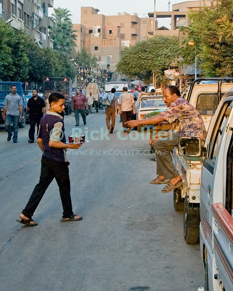 A laborer flags down a shop boy carrying coffee or tea, at the end of the day in the Sharia Ahmed Maher (street) in the old city, Cairo, Egypt.  Cairo residents and shoppers come and go, sharing the street with trucks and cars as they make their way home with shopping at the end of the day. © Rick Collier<br /> <br /> <br /> <br /> <br /> <br /> <br /> Egypt Egyptian Cairo tourist tourism history historic antiquities Islamic mosque 'old town' 'walled city' vendor seller pedestrian walk resident Arab workers laborer truck street road coffee tea cup tray