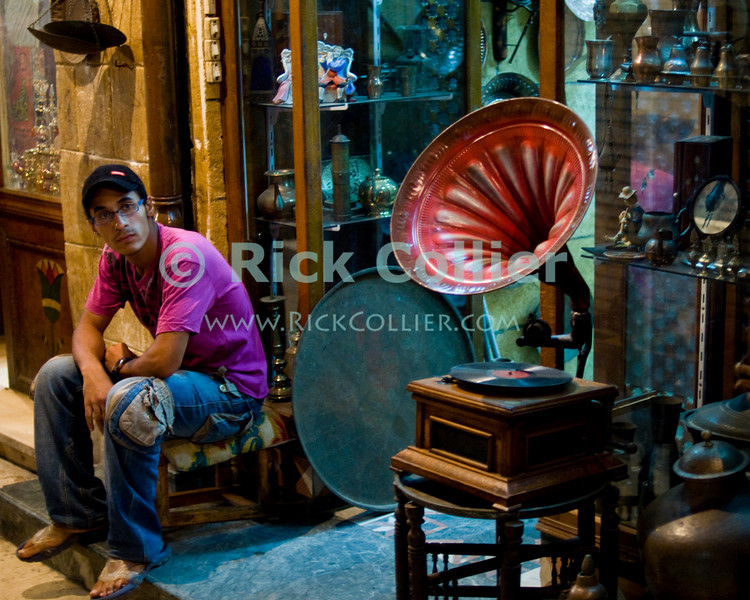 """Khan el-Khalili bazaar, Cairo, Egypt -- A shopkeeper waits for business, near quitting time on a quiet side-alley of the Khan bazaar.  (Subject permission / release is available.) © Rick Collier / RickCollier.com<br /> <br /> <br /> <br /> <br /> travel; vacation; destination; Egypt; Cairo; night; Khan; """"Khan el-Khalili""""; bazaar; market; marketplace; lights; shops; stalls; vendors; portrait; shop; shopkeeper;"""