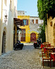 Rhodes Town, on the island of Rhodes, Greece.  Tables await the evening social scene at a small taverna in a narrow alley. © Rick Collier<br /> <br /> <br /> <br /> <br /> <br /> Greece Rhodes tour tourism tourist tourists citadel fort fortress castle crusader crusaders knight knights templar templars pedestrian walk walking shops stores wall walls restaurant cafe cafes tavern taverna tavernas sidewalk window windows shop shops shoppers narrow alley road
