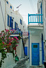 Mikonos, Greece.  Wandering off the main path in Mikonos, the visitor can find a warren of neat, clean small alleys overlooked by a variety of colorful doors, windos, and balconies.  © Rick Collier<br /> <br /> <br /> <br /> <br /> <br /> <br /> Greece Mikonos Mykonos tour tourist tourism Greek narrow alley alleyway flower flowers stairs door doors window windows shutters color colorful local paint