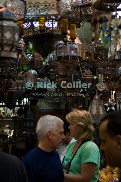 """Khan el-Khalili bazaar, Cairo, Egypt -- A few patrons is a crowd a very small lamp and metal goods shop in the Khan bazaar.  (Subject permission / release is available.) © Rick Collier / RickCollier.com<br /> <br /> <br /> <br /> <br /> travel; vacation; destination; Egypt; Cairo; night; Khan; """"Khan el-Khalili""""; bazaar; market; marketplace; lights; shops; stalls; vendors; shop; shopkeeper; metal; lamps"""