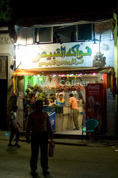 Cairo, Egypt -- Small shops like this grocery stay open late at night during the holy month of Ramadan. © Rick Collier / RickCollier.com<br /> <br /> <br /> <br /> <br /> travel; vacation; destination; Egypt; Cairo; night; bazaar; market; marketplace; lights; street; shops; stalls; vendors; crowds; pedestrians; shoppers;