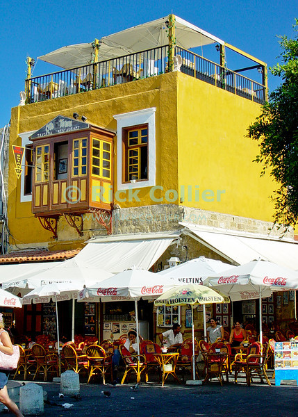Rhodes Town, on the island of Rhodes, Greece.  Diners enjoy relief from the glaring sun, under the shade of awnings and umbrellas at this brightly-colored taverna.  © Rick Collier<br /> <br /> <br /> <br /> <br /> <br /> Greece Rhodes tour tourism tourist tourists citadel fort fortress castle crusader crusaders knight knights templar templars wall walls sidewalk window windows shop store shops stores sidewalk street alley arch arches walk walking tavern taverna restaurant cafe