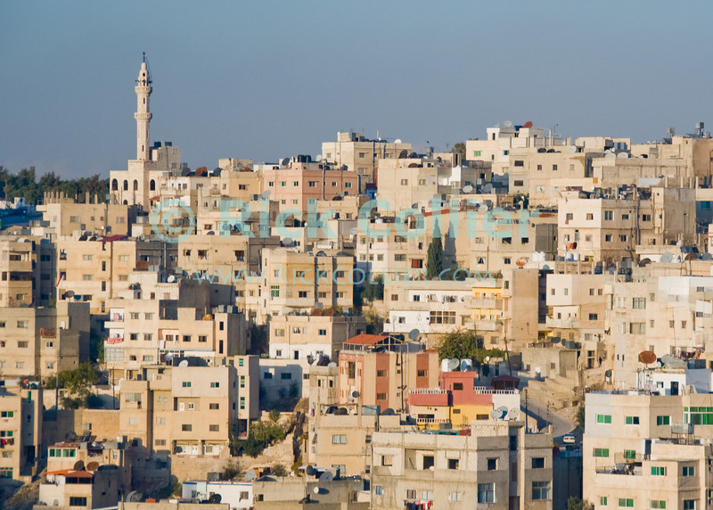 A mosque overlooks a neighborhood in Amman, Jordan.  © Rick Collier<br /> <br /> <br /> <br /> <br /> <br /> <br /> Jordan Amman Rome city Islamic buildings apartments 'city center' street mosque minaret skyline flag flagpole city panorama panoramic view cityscape