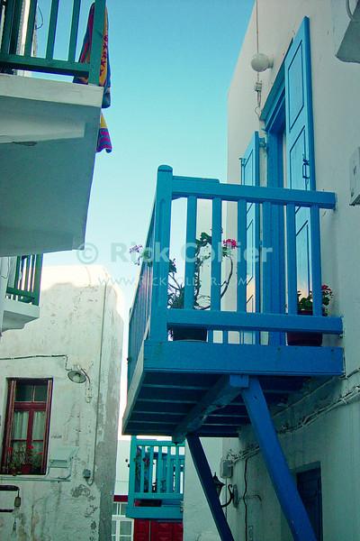 Mikonos, Greece.  Colorful balconies and windows overlook one-another in the back streets of Mikonos.  © Rick Collier<br /> <br /> <br /> <br /> <br /> <br /> <br /> Greece Mikonos Mykonos Greek balcony door window shutter alley alleyway overlook