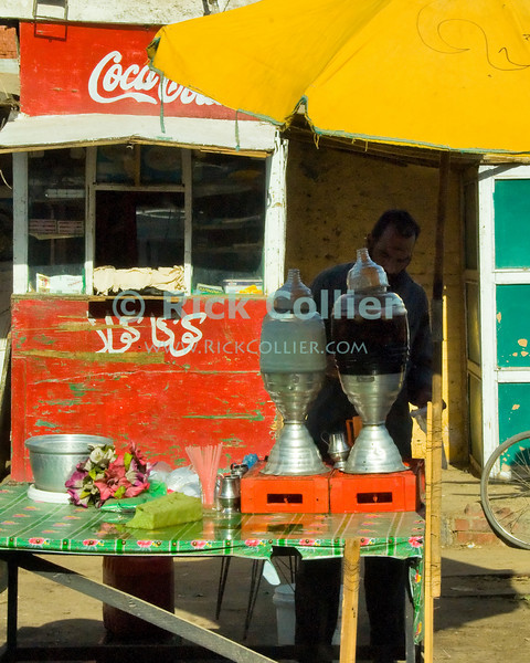 Cairo, Egypt -- A small vendor has set up a tea stand alongside the road in the outskirts of Cairo. © Rick Collier / RickCollier.com.<br /> <br /> <br /> <br /> <br /> <br /> travel; vacation; tour; tourism; tourist; destination; Egypt; Cairo; shop; vendor; stand; stall; tea; drink; refreshment; shopkeeper;
