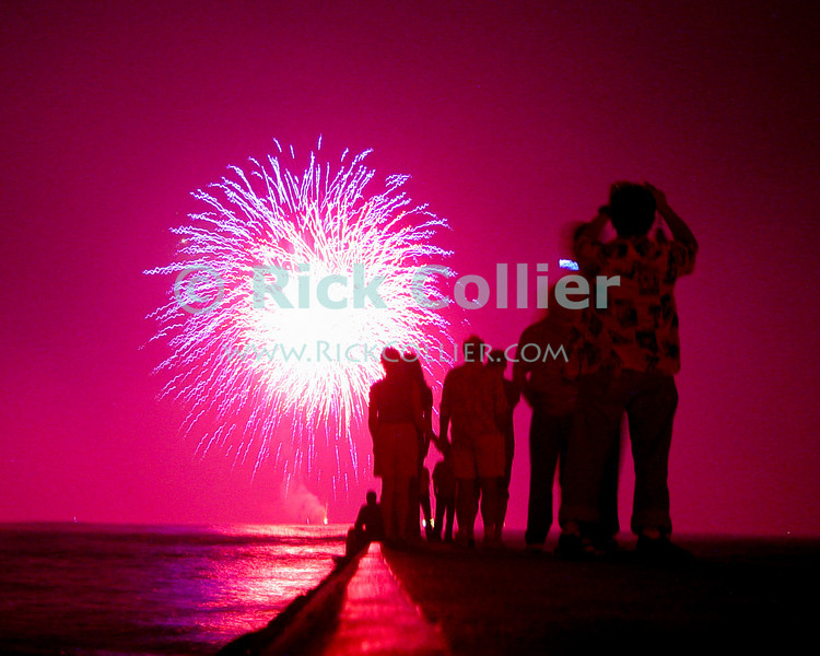 Tourists and locals gather on a jetty at Waikiki beach to watch the fireworks on New Year's eve.  Waikiki, Honolulu, Oahu, Hawaii.