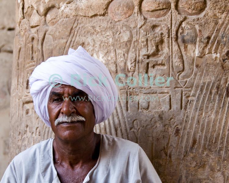 "Luxor, Egypt -- A local fellahin in Karnak Temple.  (Subject permission / release is available.) © Rick Collier / RickCollier.com.<br /> <br /> <br /> <br /> <br /> <br /> travel; vacation; tour; tourism; tourist; destination; Egypt; Luxor; Karnak; ""Karnak Temple""; Amun; Amon; Amon-Ra; temple; hieroglyph; hieroglyphic; ""ancient Egypt""; archeology; archeological; ruin; Ramses; pylon; wall; portrait"