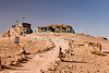 """View"" -- A bedouin businessman has set up a tent to house his jewelry shop at the highest overlook point, beyond the ""monestary"" at the top of Petra.  © Rick Collier<br /> <br /> <br /> <br /> Jordan Petra Nabatea Nabatean Rome Roman ruin archeology 'ancient world' antiquity cave 'cave dwelling' antiquities Bible Biblical civilization history historic desert stone cliff wall carve carved facade tourist tourism archeology tomb tombs valley desert path walk shop view overlook donkey"