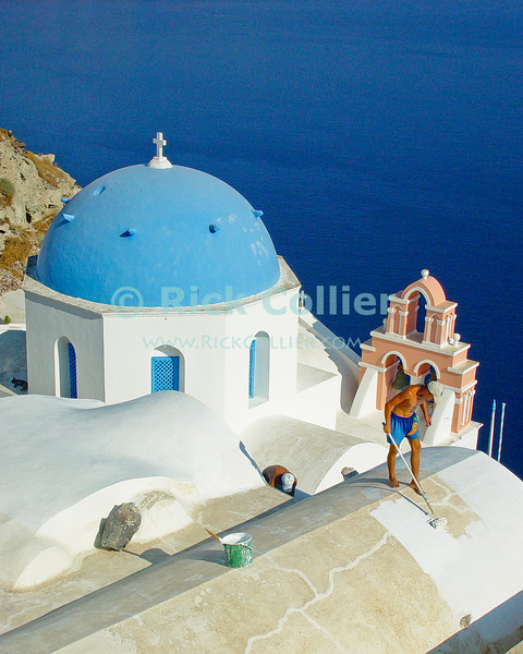 Oia Town, Santorini, Greece.  A rooftop is whitewashed, next door to the blue dome of a Greek Orthodox church.  Santorini is one of several islands that ring the blown-out remains of an ancient volcano, rising from the deep ocean in the Aegean Sea.  The volcano exploded, leaving several islands surrounding a very deep patch of sea -- actually once the caldera of the volcano.  The two large towns on Santorini, Oia and Fira towns, overlook the caldera.  © Rick Collier<br /> <br /> <br /> <br /> <br /> <br /> Greece Santorini Oia cliff cave home caldera Aegean Sea ocean sun stairs steps bright colors door doors window windows patio porch wall house home cottage bungalow table chairs flowers door doors window windows work worker cross bell belltower whitewash paint painting