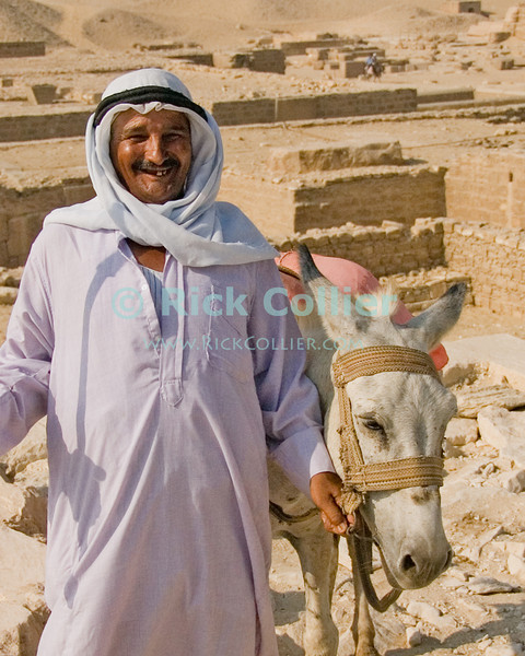 Donkey Ride?  A bedouin offering donkey rides poses at Zoser's Funerary Complex in Saqqara, Egypt.  The famous 'Step Pyramid of Zoser (or Djoser, or Doser) is among the oldest pyramids in Egypt, was designed and built by Imhotep, who was the pharoe's architect.  The 'step pyramid' style predates the more famous smooth-sided pyramids found in Giza. © Rick Collier<br /> <br /> <br /> <br /> <br /> <br /> <br /> Egypt Egyptian Cairo Saqqara pyramid pyramids step steps pharoah pharoahs Zoser Dozer Doser Djoser 'step pyramid' Imhotep tourist tourism history historic antiquities 'ancient Egypt' ancient antiquity audience tomb tombs donkey Bedouin vendor ride