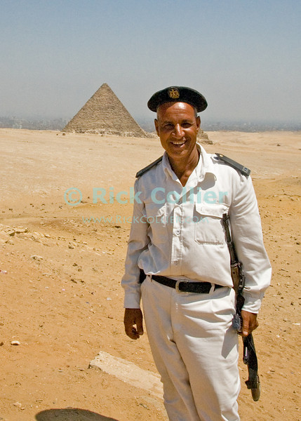 "A member of the Egyptian Antiquities Police poses for a photo, after showing the photographer the ""best"" vantage point for a picture of the pyramids.  The Pyramid of Mycerinus stands in the background.  © Rick Collier<br /> <br /> <br /> <br /> <br /> <br /> <br /> Egypt Egyptian Cairo Giza pyramid pyramids Sphinx Cheops Mycerinus Chephren guard police 'antiquities police' 'Great Pyramid' 'Great Pyramid of Cheops' Chephren 'Pyramid of Chephren' Mycerinus 'Pyramid of Mycerinus' queen queens 'Queen's Pyramids' 'Queens Pyramids' tourist tourism history historic antiquities 'ancient Egypt' ancient antiquity tomb tombs"
