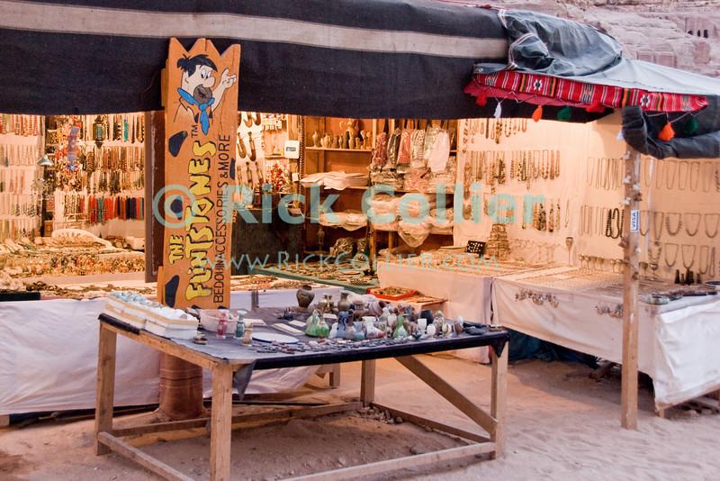 """Flintstones Shop"" -- A bedouin souvenir stand along the path in Petra, Jordan.  © Rick Collier<br /> <br /> <br /> <br /> Jordan Petra Nabatea Nabatean Rome Roman ruin archeology 'ancient world' antiquity cave 'cave dwelling' antiquities Bible Biblical civilization history historic desert stone cliff wall carve carved facade tourist tourism arab bedouin shop store jewelry souvenir"