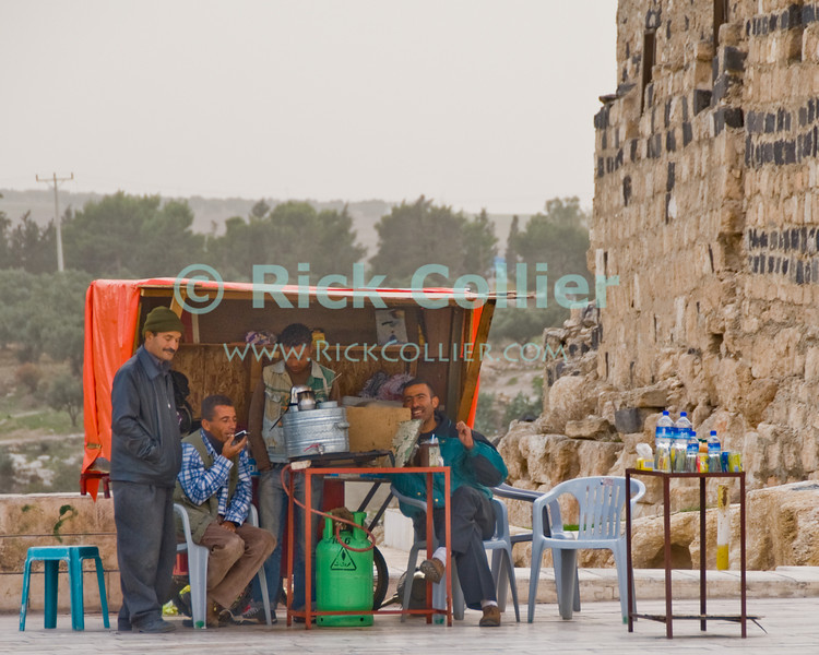 """""""Snack Shop"""" -- Four local men relax at the only refreshment stand outside the ruins of Gadara, at Umm Qais, northwestern Jordan.  © Rick Collier<br /> <br /> <br /> <br /> Jordan 'Umm Qais' Ottoman Roman Gadara Gadarenes Bible Biblical ruin ruins 'ancient world' archeology 'archeological site' antique hut shelter refreshment snack shop Arab shopkeeper friends friend laughter tea smoke smoking phone 'cell phone'"""