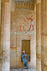 Deir el-Bahri (Temple of Hatshepsut), near Luxor, Egypt.  A tired tour guide rests in a niche in a shaded portion of  Hatshepsut's temple (also tomb).  Above his head is the only extant heiroglyphic representation of Hatshepsut.  This picture was actually defaced like all others in theis temple, but it was restored after the fact by one of her successors, Ramses.  Hatshepsut was scourged by her successors, as the only woman who ever had the temerity to rule Egypt as a man (pharoah).  © Rick Collier<br /> <br /> <br /> <br /> <br /> <br /> <br /> Egypt Egyptian Karnak Luxor tourist tourism history historic antiquity antiquities Thebes Theban Thebian Nile 'Nile River' temple monument Hatshepsut pharoah 'Deir el-Bahri' heirglyph heiroglyphic