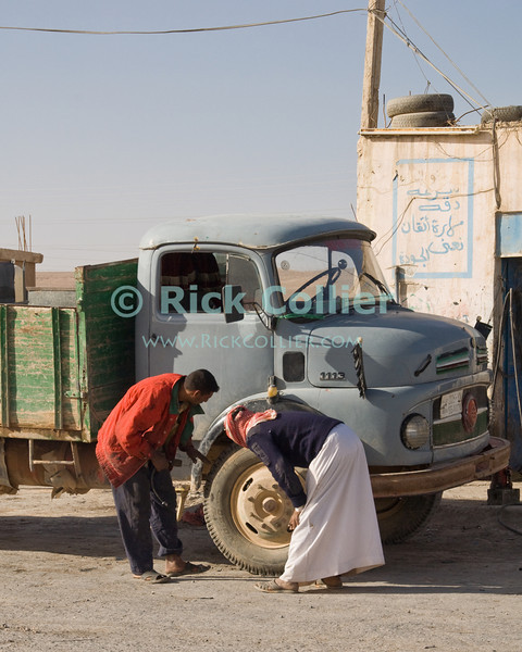 """""""Broken"""" -- A truck driver consults with the local mechanic (in traditional arab garb) at a truck stop on the """"desert highway,"""" south from Amman Jordan.  © Rick Collier<br /> <br /> <br /> <br /> Jordan truck 'truck stop' garage repair arab driver bedouin arab mechanic wheel arabic country desert"""