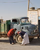 """Broken"" -- A truck driver consults with the local mechanic (in traditional arab garb) at a truck stop on the ""desert highway,"" south from Amman Jordan.  © Rick Collier<br /> <br /> <br /> <br /> Jordan truck 'truck stop' garage repair arab driver bedouin arab mechanic wheel arabic country desert"