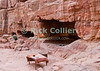 """Petra Storefront"" -- A bedouin's desk and chest await the next day's buisiness, as does the Nabatean lodgings the family uses to shelter from the sun throughout the long days.  Petra, Jordan.  © Rick Collier<br /> <br /> <br /> <br /> Jordan Petra Nabatea Nabatean Rome Roman ruin archeology 'ancient world' antiquity cave 'cave dwelling' antiquities Bible Biblical civilization history historic desert stone cliff wall carve carved facade tourist tourism archeology tomb tombs valley path road hike trail desert necropolis steps stairs arab bedouin vendor table desk chest office space"