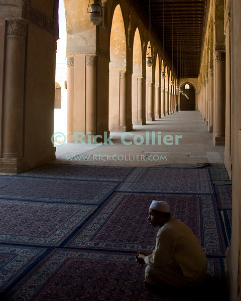 "Cairo, Egypt -- Bright light shines through lovely arched openings into the arcades surrounding the central plaza and fountain at the historic ibn Tulun mosque.   © Rick Collier / RickCollier.com<br /> <br /> <br /> <br /> travel; vacation; tour; tourism; tourist; destination; Egypt; Cairo; mosque; madrassa; Tulun; ""ibn Tulun""; arcade; arch; arches; archways; passage; rug; carpet; ""prayer rug"";"