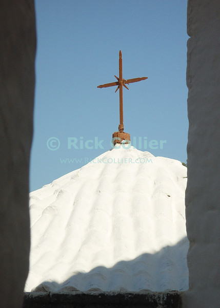 Patmos, Greece.  A wrought iron cross stands atop the chapel to St. John, at the site of the Cave of the Revelations on Patmos Island, Greece.  © Rick Collier<br /> <br /> <br /> <br /> <br /> <br /> Greece Patmos cross religion Christian John Saint John 'St John' revelation Bible Biblical Book of Revelations cave holy site