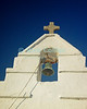 Mikonos, Greece.  A bell hangs over the door of many small Greek Orthodox chapels in the Greek islands.  © Rick Collier<br /> <br /> <br /> <br /> <br /> <br /> <br /> Greece Mikonos Mykonos Greek Orthodox church chapel bell tower stone whitewash cross christian