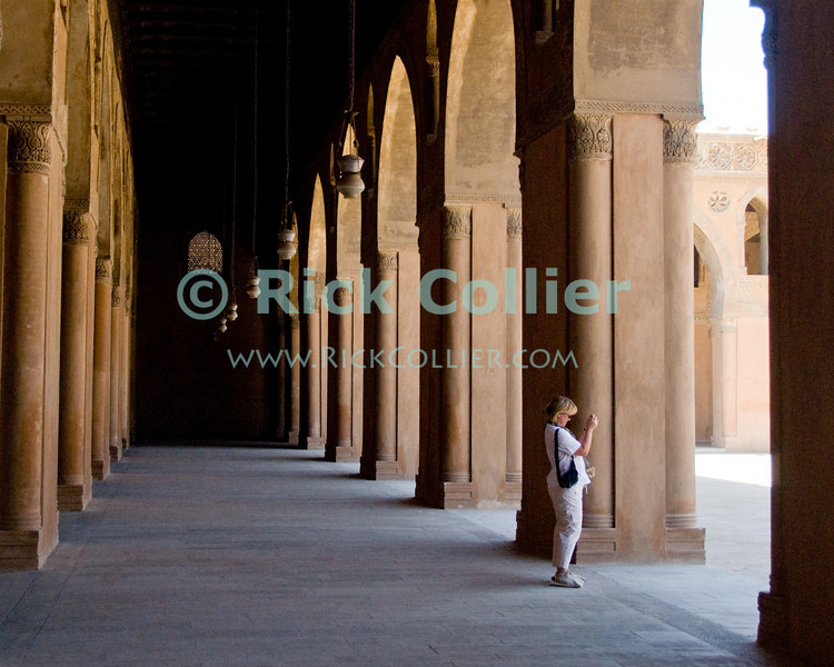 """Cairo, Egypt -- Bright light shines through lovely arched openings into the arcades surrounding the central plaza and fountain at the historic ibn Tulun mosque.   © Rick Collier / RickCollier.com.<br /> <br /> <br /> <br /> <br /> <br /> travel; vacation; tour; tourism; tourist; destination; Egypt; Cairo; mosque; madrassa; Tulun; """"ibn Tulun""""; arcade; arch; arches; archways; passage; lamp; lamps"""