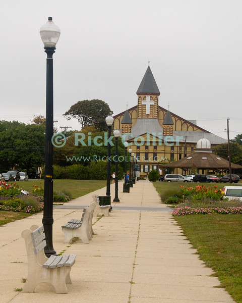 """""""Meeting Hall"""" - Founded as a Christian prayer camp at the beach, Ocean Grove, New Jersey is anchored at its center by a grand meeting hall.<br /> <br /> <br /> USA """"New Jersey"""" NJ """"Ocean Grove"""" Ocean Grove sidewalk meeting hall conference center lamp light streetlight path bench benches yard garden"""