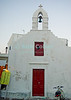 Mikonos, Greece.  A Greek Orthodox chapel used by locals is frequently not as pristine and freshly painted as the ones frequented by tourists.  © Rick Collier<br /> <br /> <br /> <br /> <br /> <br /> <br /> Greece Mikonos Mykonos tour tourist tourism Greek Orthodox church bell tower cross door window belfry local paint