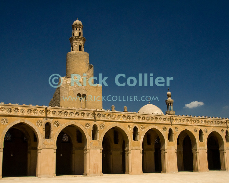 """Cairo, Egypt -- The unique spiral minaret towers over the walls and arcade at the historic ibn Tulun mosque. © Rick Collier / RickCollier.com.<br /> <br /> <br /> <br /> <br /> <br /> travel; vacation; tour; tourism; tourist; destination; Egypt; Cairo; mosque; madrassa; Tulun; """"ibn Tulun""""; minaret; """"spiral minaret""""; wall; walls; arcade; arches; arch"""