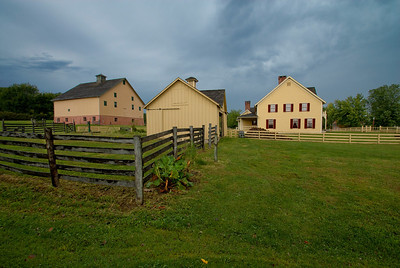 This image shows the Tangen residence, buggy barn and the main barn. They are located at the edge of Walnut Hill at Living History Farms.